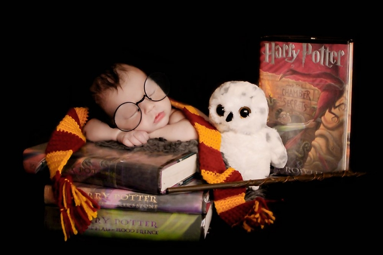 Harry Potter themed newborn photosession. Baby William is laying on a stack of Harry Potter books, holding a wand, Harry Potter round glasses, wearing a Gryffindor scarf, stuffed owl, used as props.