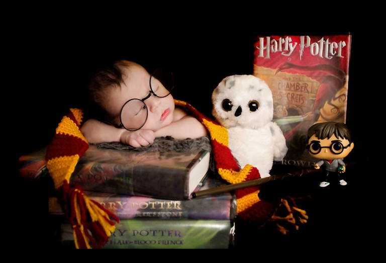 Harry Potter themed newborn photosession. Baby William is laying on a stack of Harry Potter books, holding a wand, wearing a Gryffindor scarf, Harry Potter round glasses, stuffed owl, and a Harry Potter Funko Pop doll used as props.