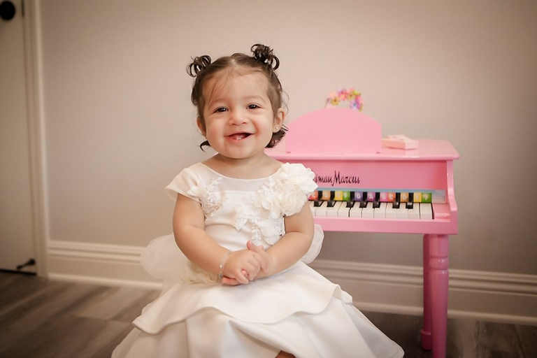 Christina turns one and celebrates with her Cake Smash. Pre cake wearing a white dress and sitting next to her mini piano. Big smile.