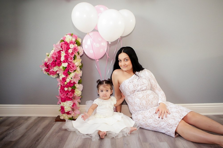 Christina turns one and celebrates with her Cake Smash. Pre cake wearing a white dress and sitting next to her mom.
